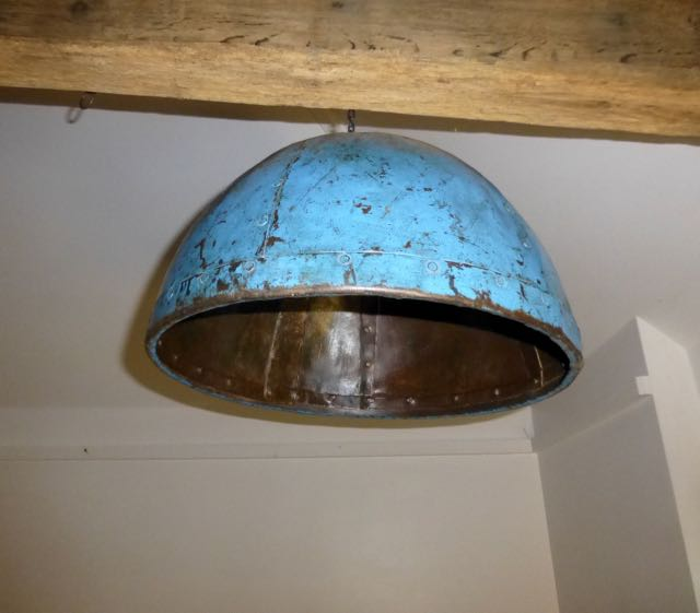 One of a pair of blue pendant lights